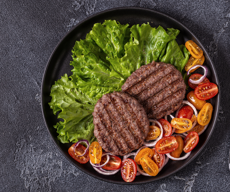 Photo of burger patties with lettuce and tomatoes